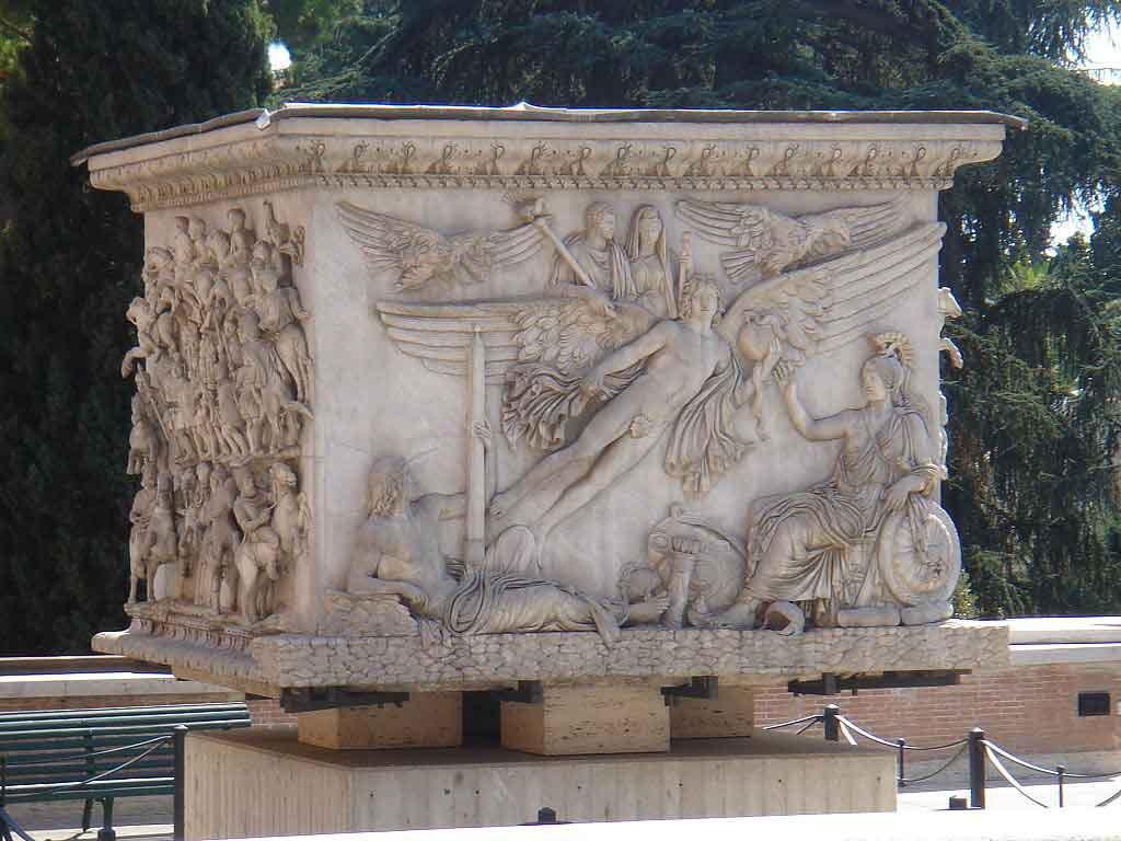 Base della colonna di Antonino Pio, conservata ai Musei Vaticani: sulla sinistra, il genio del Campo Marzio che tiene l'obelisco di Montecitorio